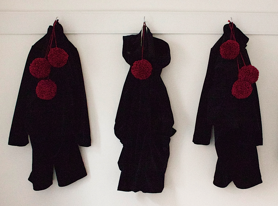 Carin Mansfield, Slow Fashion designer, Universal Utility, In-ku, black jackets and red pom poms on white wall | Fabulous Fabsters