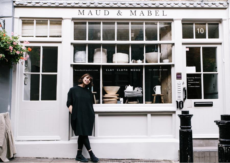 Woman with brown hair and black dress stands in front of simple shop front with ceramics in the windows. Maud & Mabel