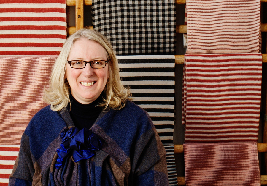 Founder of Selvedge, a textile magazine, Polly Leonard in front of blue and red textiles. Photo by Richard Nicholson.