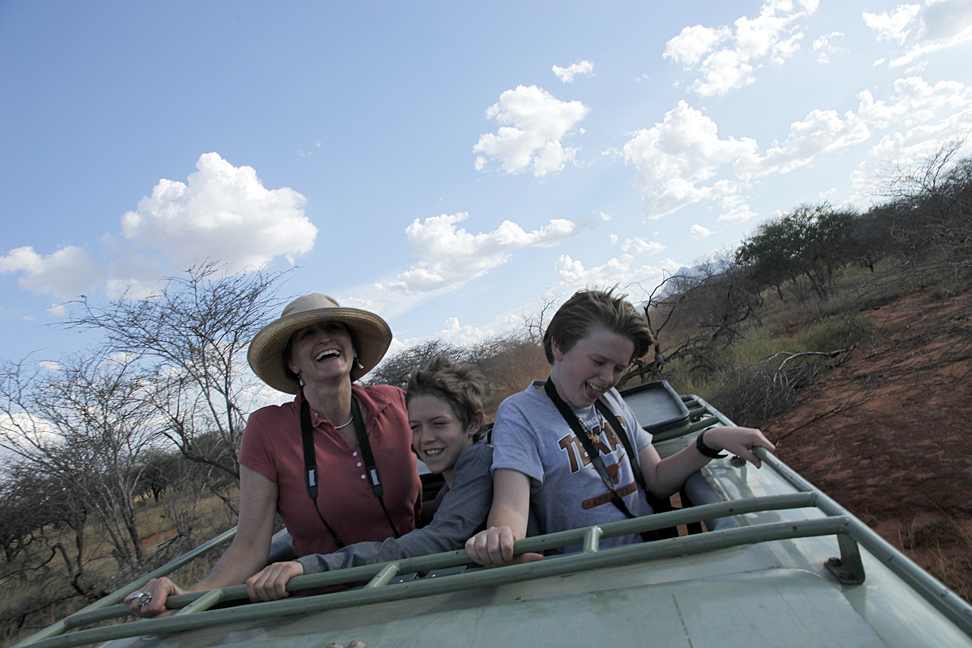 Mother and two sons riding in jeep through safari, Jeannie Ralston