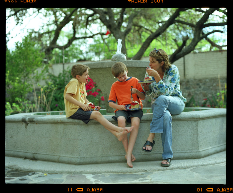 Mother and two sons sitting on edge of courtyard fountain, Jeannie Ralston, San Miguel de Allende