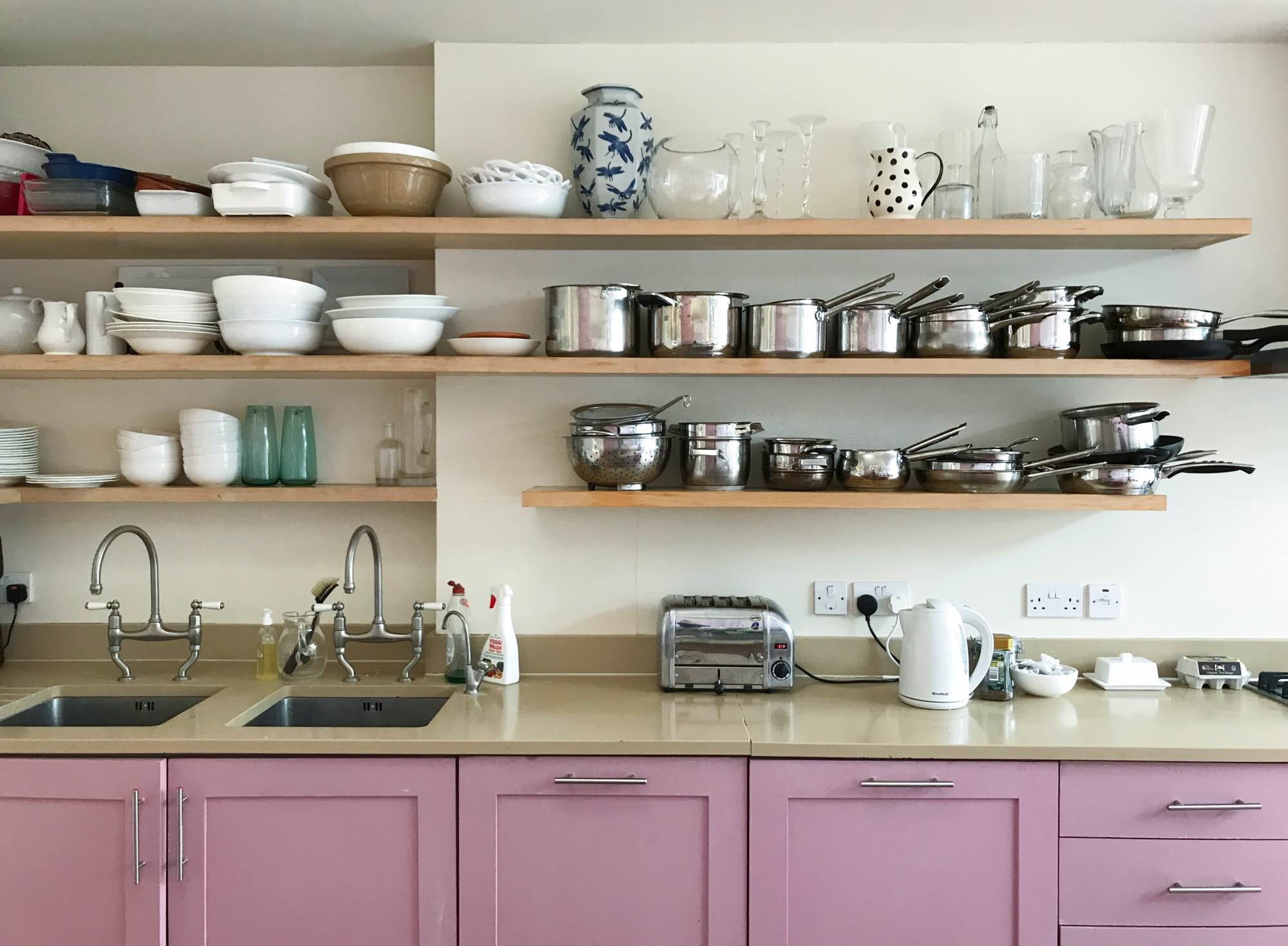 Open shelving in kitchen with pink cupboards
