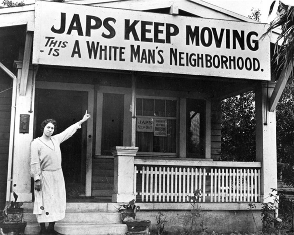 Woman pointing to anti-Japanese sign on front of her house