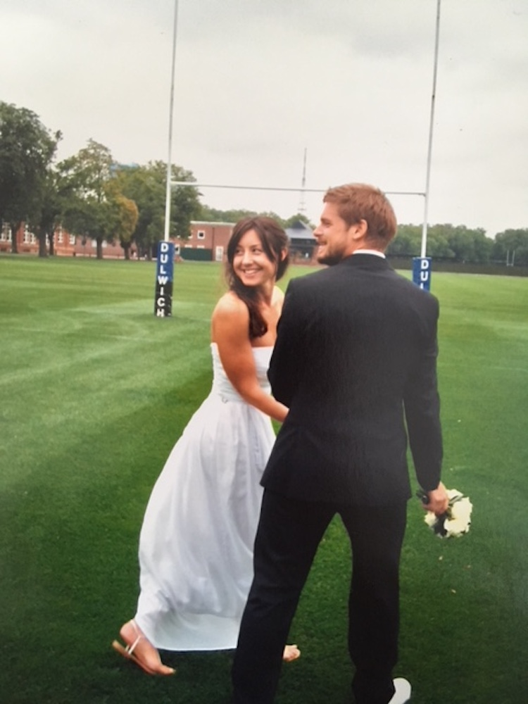 Bride and groom holding hands on a rugby pitch