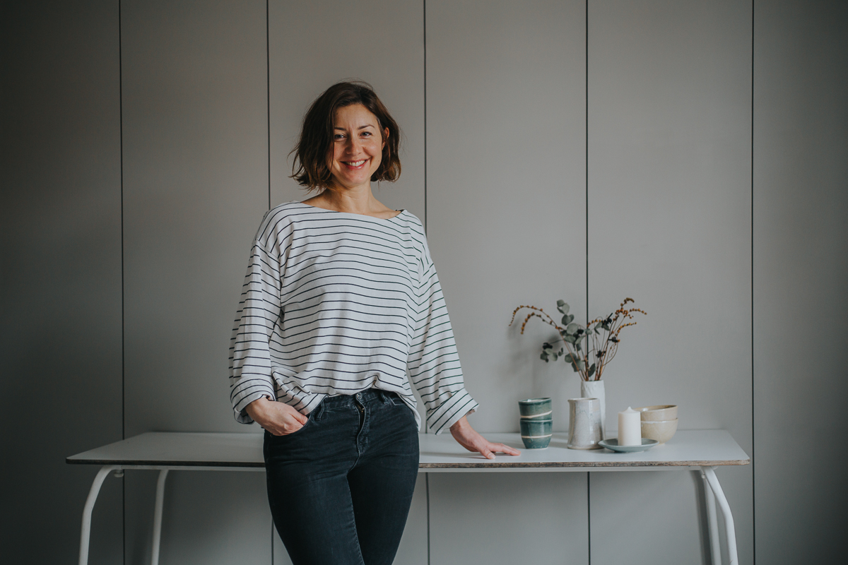 Emily Mathieson of Aerende — ethical interiors, life-improving homewares, Woman in striped shirt and jeans in front of table with homewares