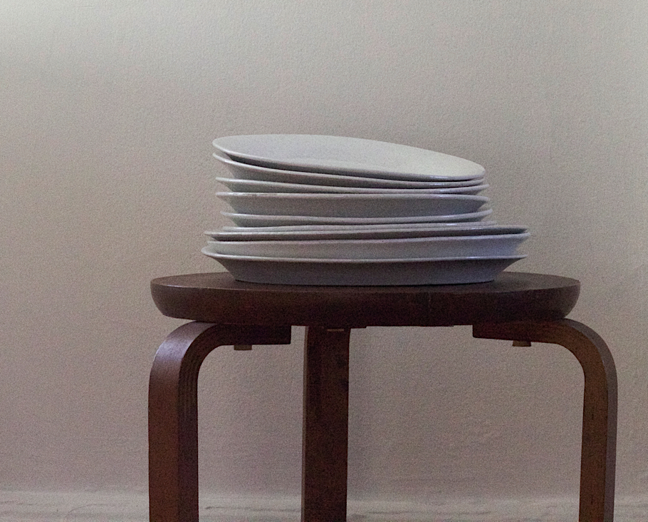 Julie Carlson Brooklyn Apartment, Stack of white plates from Bennington Pottery on three legged stool | Fabulous Fabsters