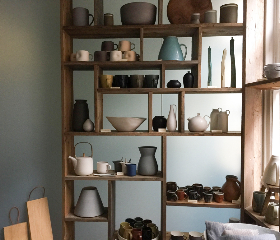 Black and white ceramic jugs, bowls and vases displayed on a Japanese Tansu shelf at Maud & Mabel