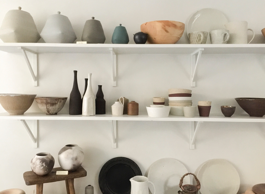 Assorted ceramics and wood objects on display on white shelves at Maud & Mabel