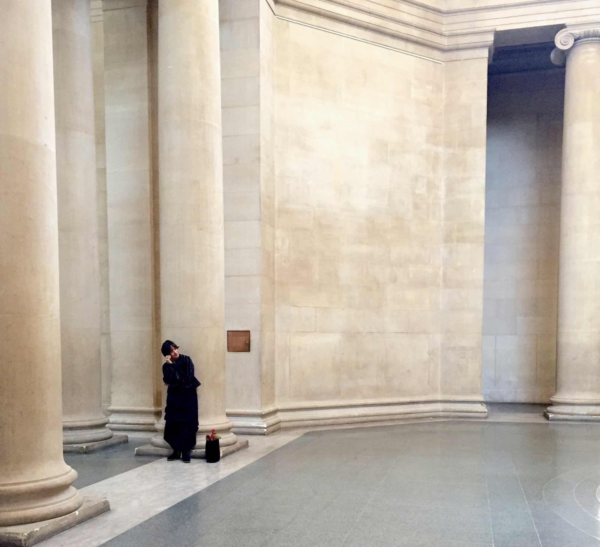 Cindy Polemis. Woman in black standing in atrium of Tate Britain.