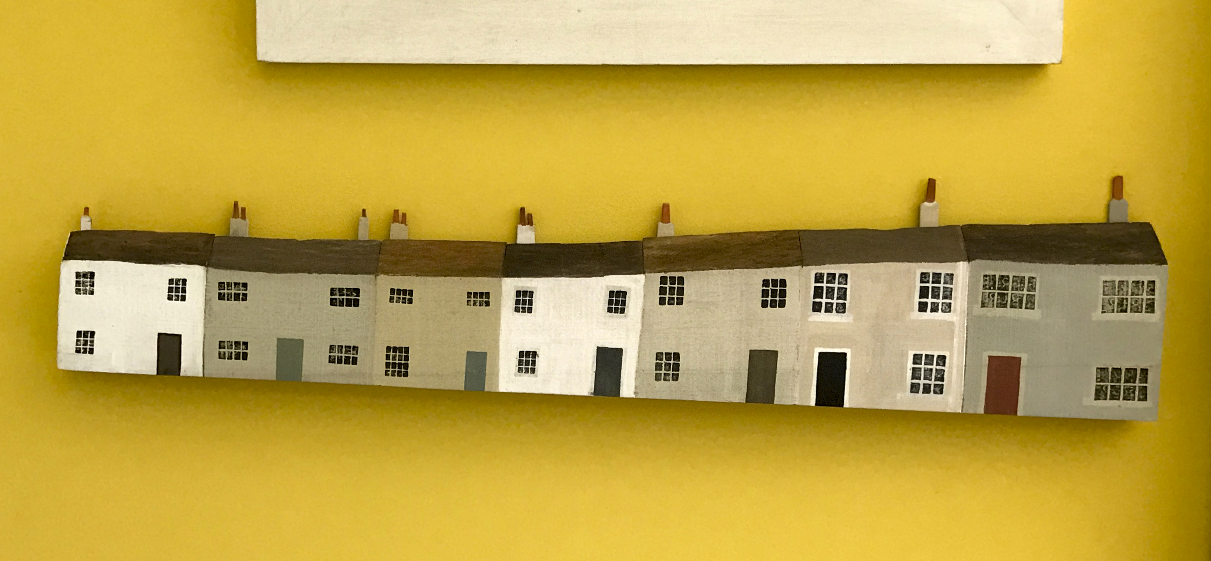 Artwork of terraced houses by Victor Stuart Graham hung on bright yellow wall