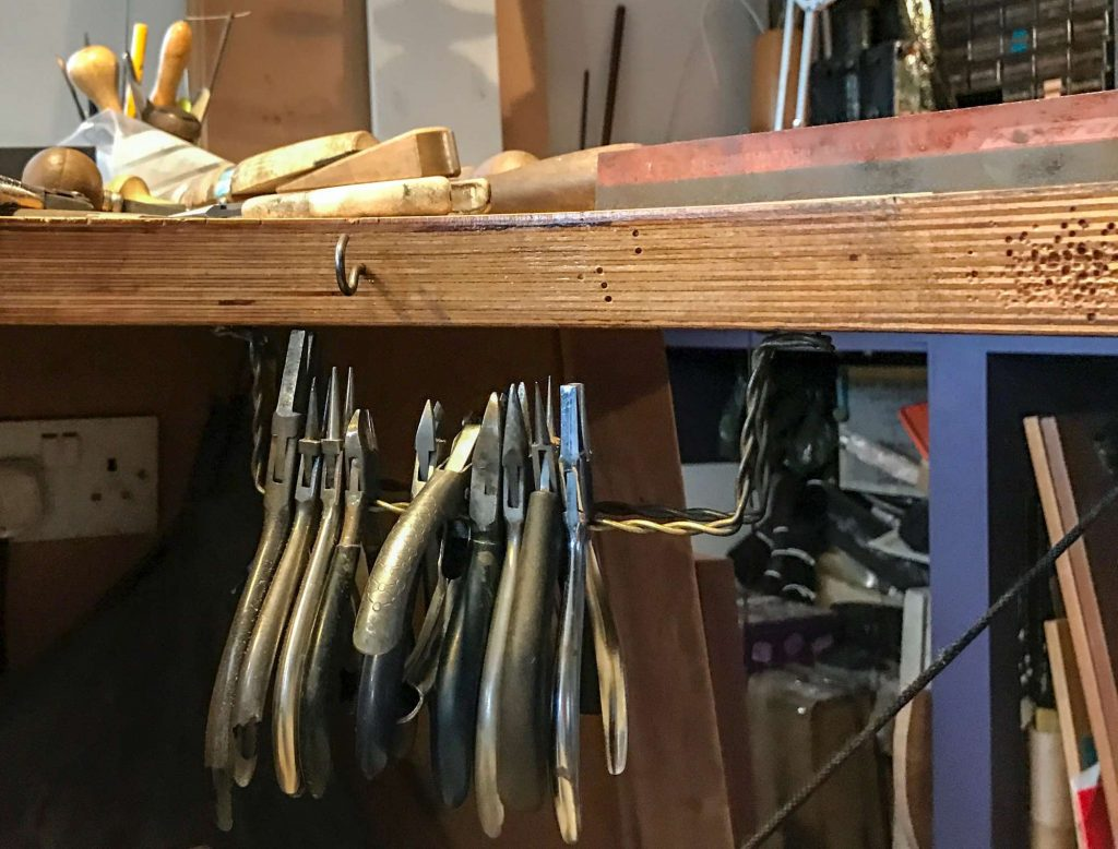 Jeweller's pliers hanging under a workbench