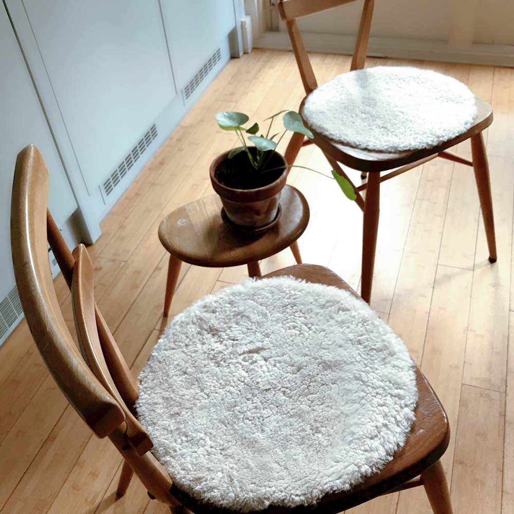 Cream sheepskin seat pads on Ercol chairs.