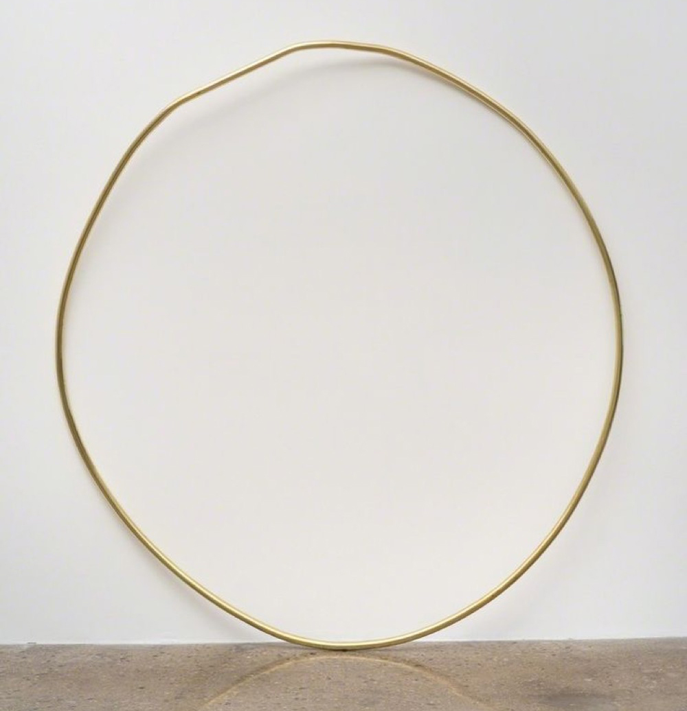 Brass circle sculpture by Mark Handforth against white wall on marble floor, Full Circle Giving