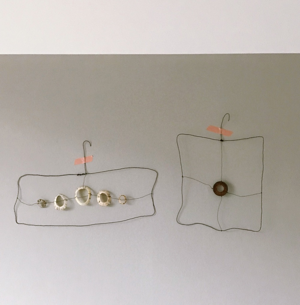 handmade wire frame with hanger holding a thread of drilled sea shells, Gathered Found Made in Etsy