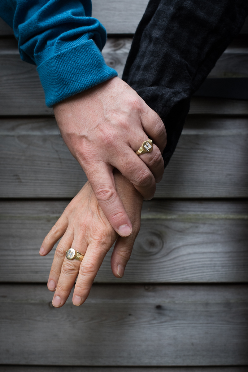 Couple wearing signet rings holding hands.
