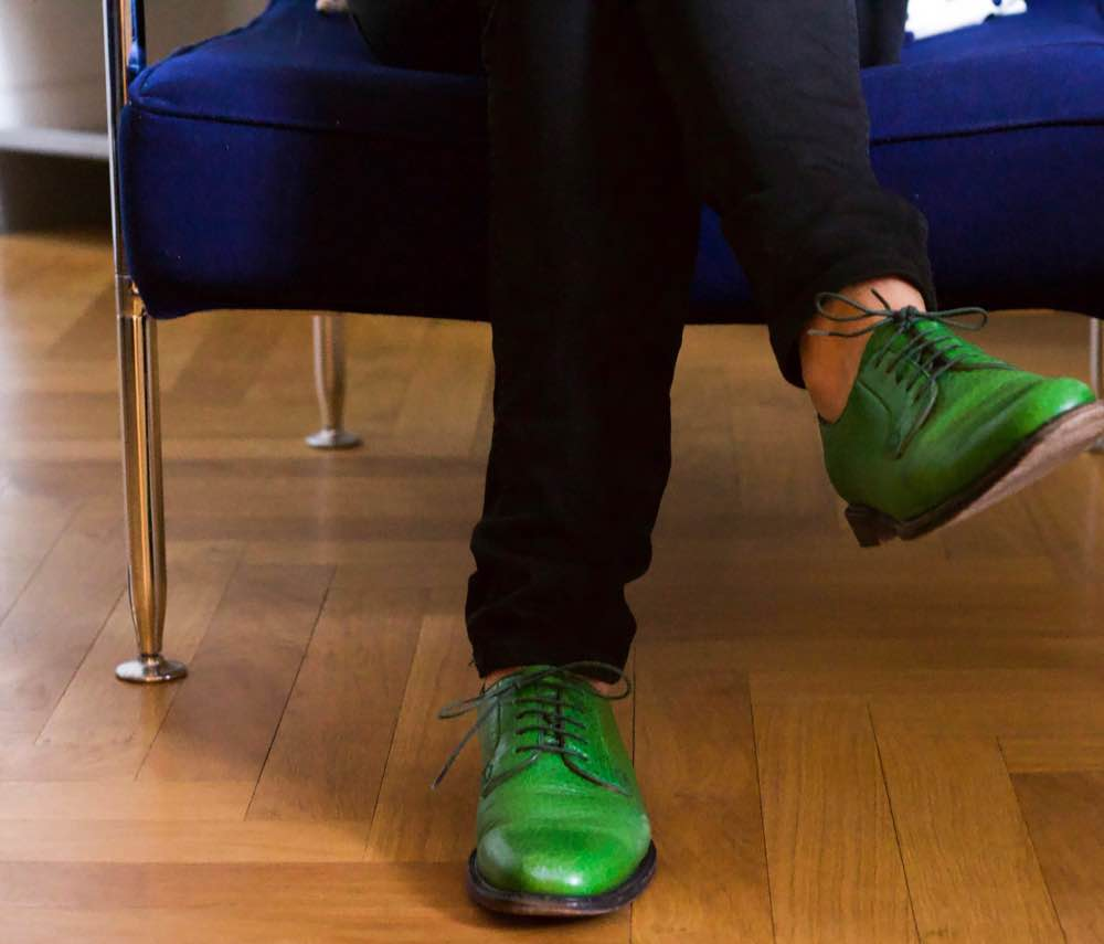 Woman in blue chair wearing black trousers and bright green brogues