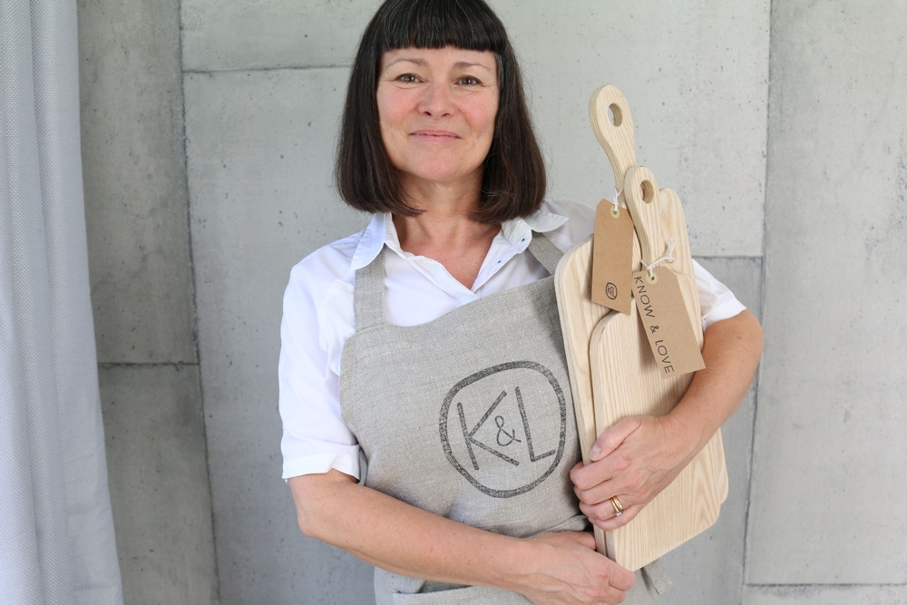 Woman holding wooden cutting boards.