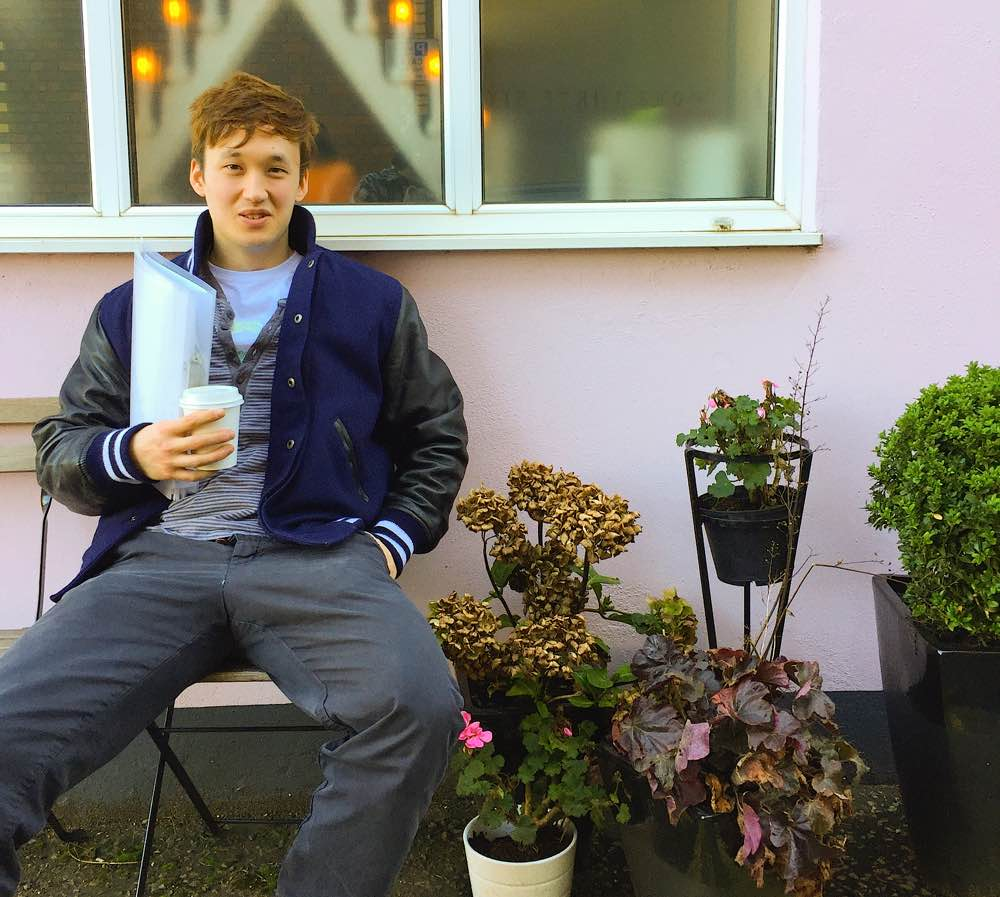 Teenage boy in front sitting in front of building in London mews