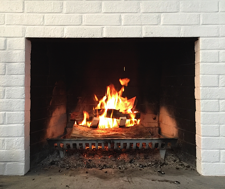 Glowing fire in fireplace with white brick surround | My Contents Have Shifted