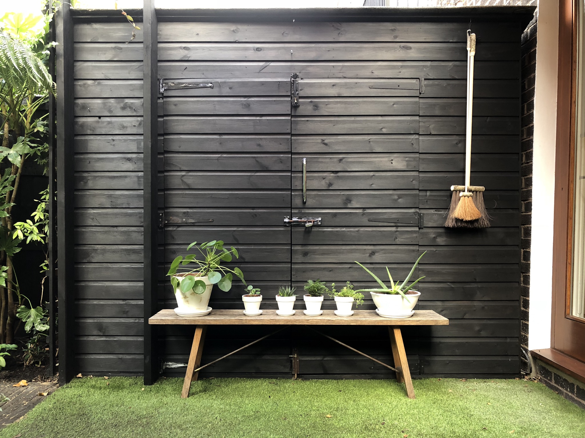 Black garden shed with bench in front and plants in white pots, paintbrush