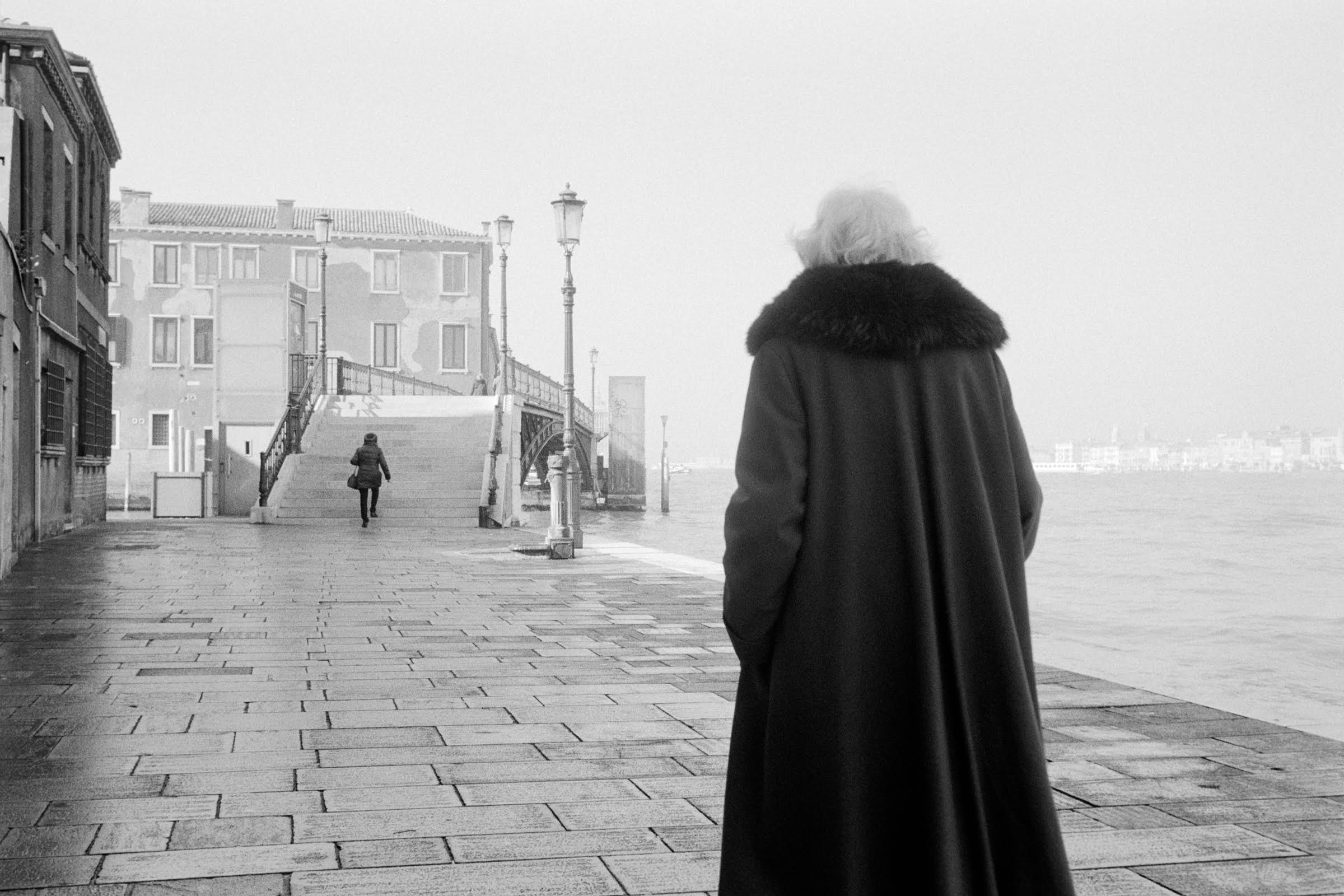 Elderly woman walking looks across the water in Venice. Roman Henze