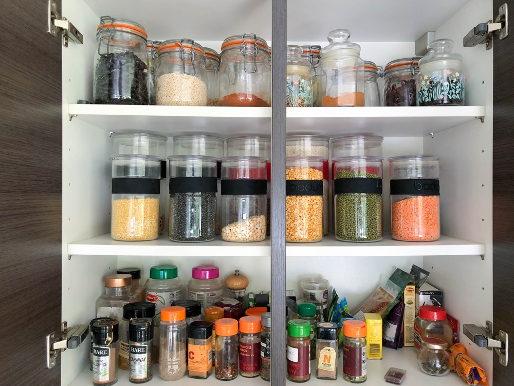 Pantry with glass jars of grains, beans and spices, Deepa Mer nutritionist