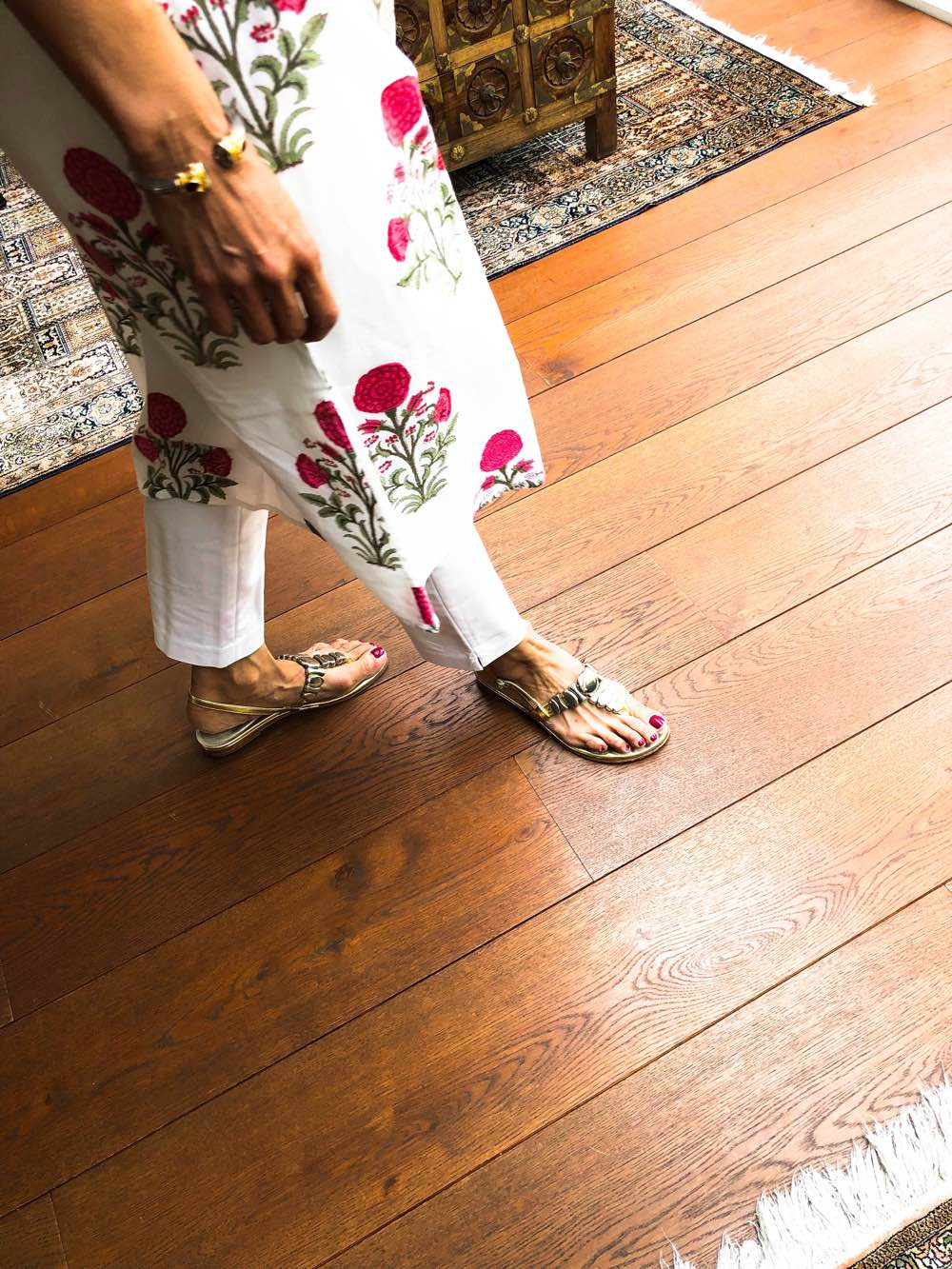 A view of a woman's feet in gold sandals with a corner of a pink and white block printed Indian dress over white trousers, Deepa Mer nutrition