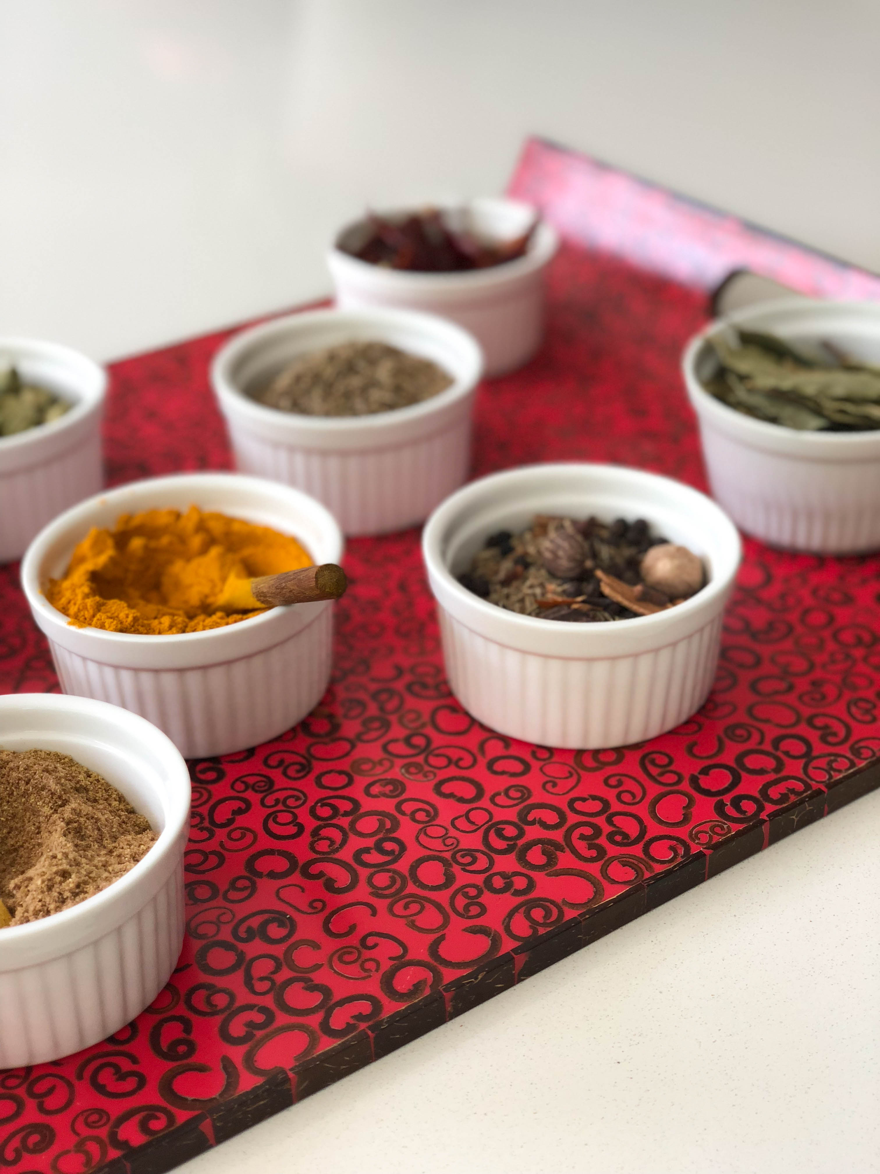 Red laquer tray with bowls of spices, Deepa Mer nutritionist